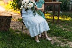 Abuela de la visita abuela, mujer mayor que sienta y que abraza su nieta, la muchacha y sostener un ramo de flores en fotos de archivo libres de regalías