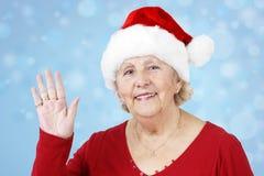 Abuela del sombrero de la Navidad que agita sobre azul Fotos de archivo libres de regalías