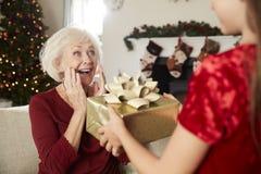 Abuela emocionada que recibe el regalo de la Navidad de nieta en casa foto de archivo