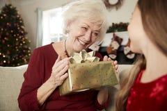 Abuela emocionada que recibe el regalo de la Navidad de nieta en casa fotografía de archivo