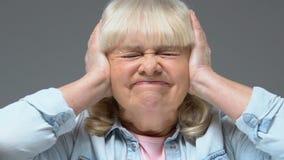 Abuela enfadada que cubre los oídos por las manos, tensión sana ruidosa, dolor de cabeza de sensación almacen de metraje de vídeo