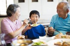 Abuela feliz que alimenta a su nieto Fotos de archivo