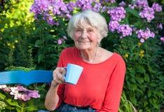 Abuela feliz que come un café en el jardín Imagen de archivo