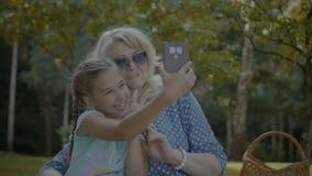 Abuela feliz que toma el selfie con el niño en parque almacen de metraje de vídeo