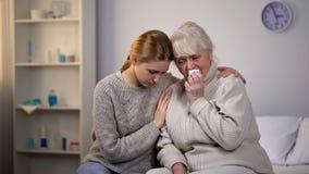Abuela gritadora de abrazo y favorable de la nieta, enfermedad incurable foto de archivo