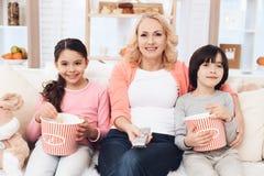 Abuela hermosa joven con sus nietos que comen las palomitas y que miran película en casa en el sofá imagen de archivo libre de regalías