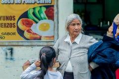 Abuela hispánica que compra una pizza para su nieta imagenes de archivo