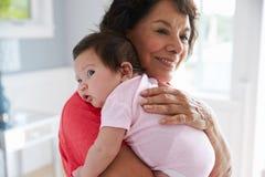 Abuela orgullosa que detiene a la nieta del bebé Foto de archivo libre de regalías