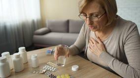 Abuela que bebe las píldoras prescritas para la angustia, diabetes sufridora de la señora mayor almacen de video