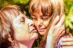 Abuela que besa a su nieta Imágenes de archivo libres de regalías