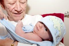 Abuela que detiene al nieto después de baño Foto de archivo libre de regalías
