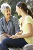 Abuela que habla con la nieta adolescente en banco Imagenes de archivo