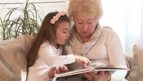 Abuela que lee un libro con su nieta metrajes