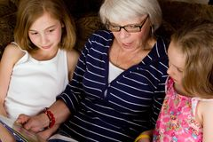 Abuela que lee un libro a los cabritos magníficos imagenes de archivo