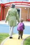 Abuela que lleva al nieto a la escuela fotos de archivo