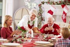 Abuela que pone en evidencia Turquía en la comida de la Navidad de la familia Foto de archivo libre de regalías