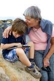 Abuela que se besa con el nieto del amor que juega con la tableta en la playa Imagenes de archivo