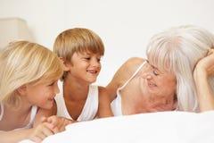 Abuela que se relaja en cama con los nietos Imagen de archivo libre de regalías