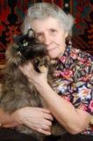 Abuela que se sienta con el gato en sus manos Fotos de archivo libres de regalías