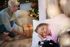 Abuela que trae un regalo de Navidad imágenes de archivo libres de regalías