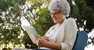 Abuela que usa la tableta en el parque Imagenes de archivo