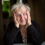 Abuela rusa Retrato de una mujer mayor que se sienta en una tabla en su casa Feliz Fotos de archivo libres de regalías
