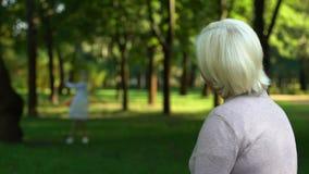 Abuela sola que recuerda su niñez feliz, sentándose en parque solamente almacen de video