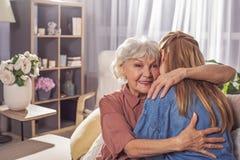 Abuela sonriente que abraza a la muchacha en sitio Foto de archivo libre de regalías