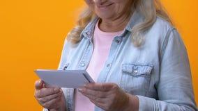 Abuela sonriente que mira las fotos viejas, admirando memorias, conmemoración de la historia almacen de video