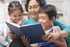 Abuela y libro de lectura de los nietos junto Imagen de archivo