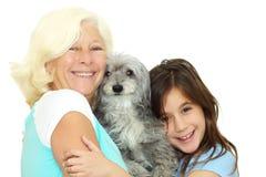 Abuela y muchacha que abrazan el perro de la familia Fotografía de archivo libre de regalías