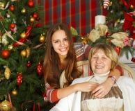 Abuela y nieta adolescente cerca del árbol de navidad Imagen de archivo