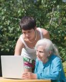 Abuela y nieta con la computadora portátil Imagenes de archivo