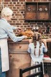 abuela y nieta felices con el pavo delicioso para la acción de gracias Fotografía de archivo libre de regalías