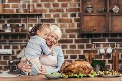 abuela y nieta que abrazan en cocina y que miran el pavo recién preparado foto de archivo