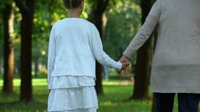 Abuela y nieta que caminan a lo largo del parque que lleva a cabo las manos, familia feliz metrajes