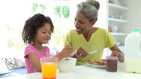 Abuela y nieta que desayunan junto almacen de video