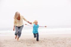 Abuela y nieta que se ejecutan a lo largo de la playa Fotos de archivo