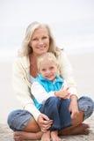 Abuela y nieta que se sientan en la playa Imágenes de archivo libres de regalías