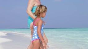 Abuela y nieta que se sientan en la playa hermosa almacen de metraje de vídeo