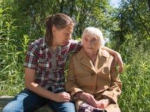 Abuela y nieta que se sientan en un banco Foto de archivo