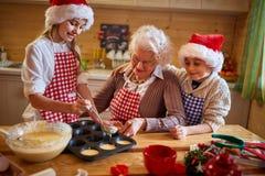 Abuela y nietos que preparan las galletas - tiempo de la familia foto de archivo