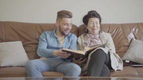 Abuelita bonita linda y nieto adulto que se sientan en casa en el sofá de cuero marrón que mira las fotos viejas en la foto grand almacen de video