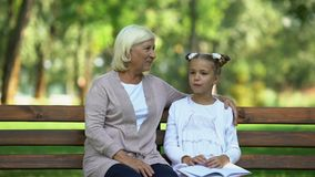 Abuelita bonita que abraza a poca nieta que escucha sus historias, chisme femenino metrajes