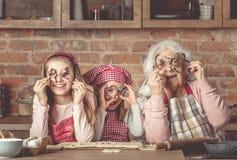 Abuelita con las nietas que miran la cámara a través de los cortadores de la galleta Foto de archivo