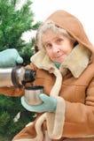 Abuelita con té caliente bajo abeto Imagen de archivo