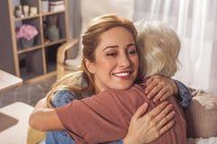 Abuelita de abrazo femenina alegre en el apartamento Imagen de archivo