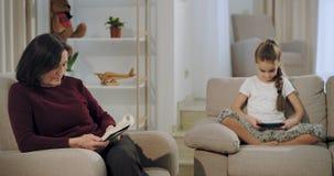 Abuelita hermosa con su sobrina que pasa una época junta en la abuelita de la sala de estar que lee un libro en el sofá y la so metrajes