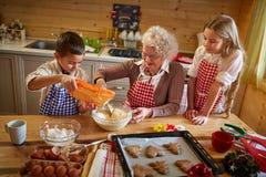 Abuelita que hace las galletas de la Navidad con los niños Imagenes de archivo