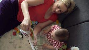 Abuelita y bebé que juegan en el sofá Libros de lectura 4K Niñera o canguro metrajes